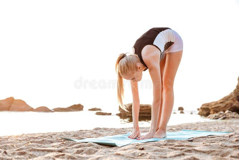 Den unga kvinnan som gör yoga, övar på mattt utomhus royaltyfria bilder