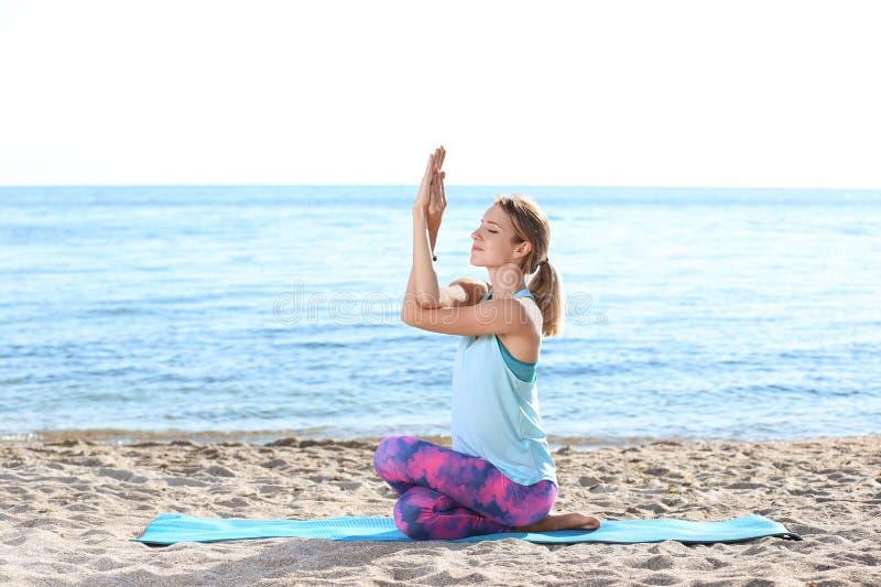 Den unga kvinnan som gör yoga, övar på stranden arkivbild