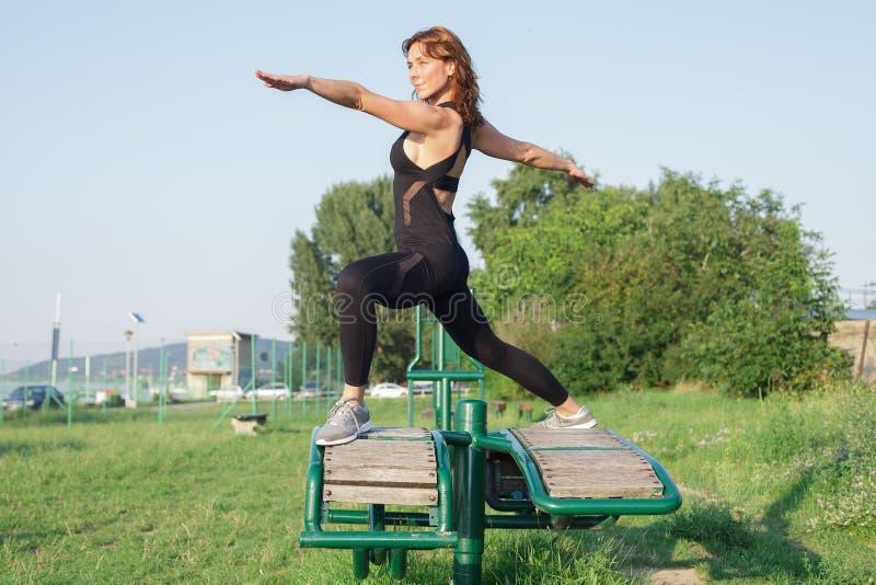 den unga kvinnan som gör yoga för krigare 2, poserar utomhus arkivbilder