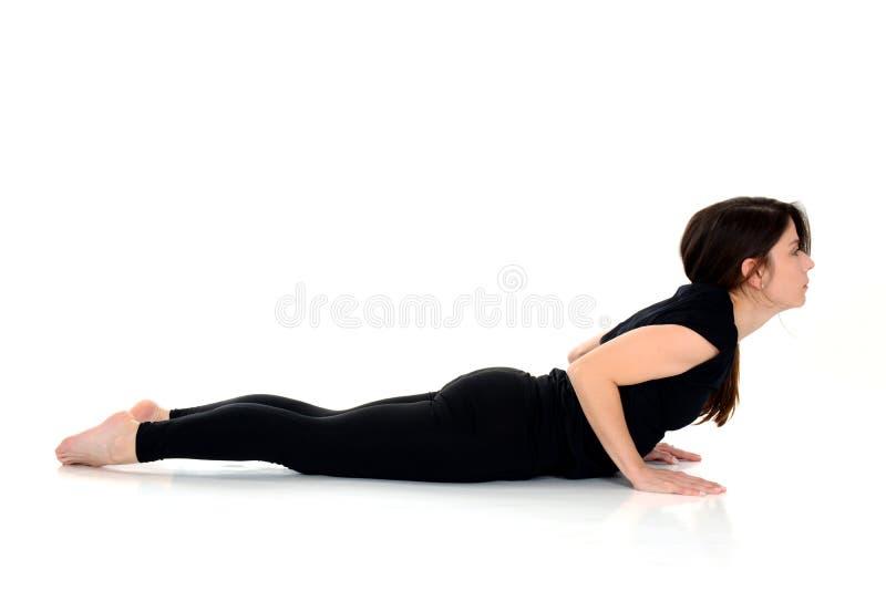 Den unga kvinnan som gör den yogaasanaBhujangasana kobran, poserar fotografering för bildbyråer