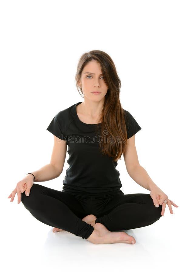 Den unga kvinnan som gör yogaasanaSukhasana lätt sammanträde, poserar royaltyfri bild