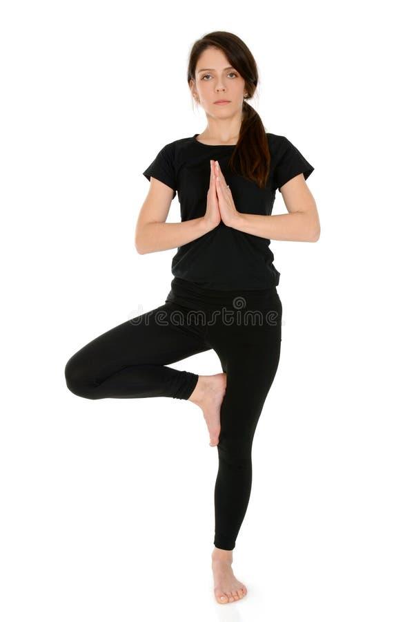 Den unga kvinnan som gör yogaasanaträdet, poserar Vrksasana royaltyfria foton