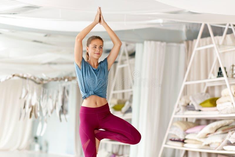 Den unga kvinnan som gör yogaträdet, poserar på studion royaltyfria bilder