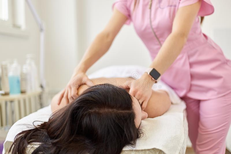 Den unga kvinnan som har tillbaka massage i skönhetsalongen som kopplar av, medan ligga på bekväm couh, tar omsorg av hennes hud  arkivbilder