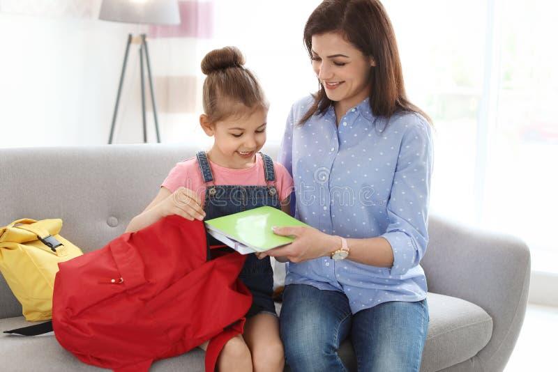 Den unga kvinnan som hjälper hennes lilla barn, får klar arkivfoton