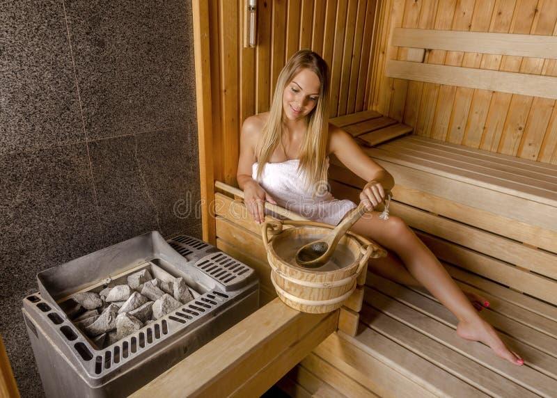 Den unga kvinnan som kopplar av i bastu och, tycker om den varma luften royaltyfri fotografi