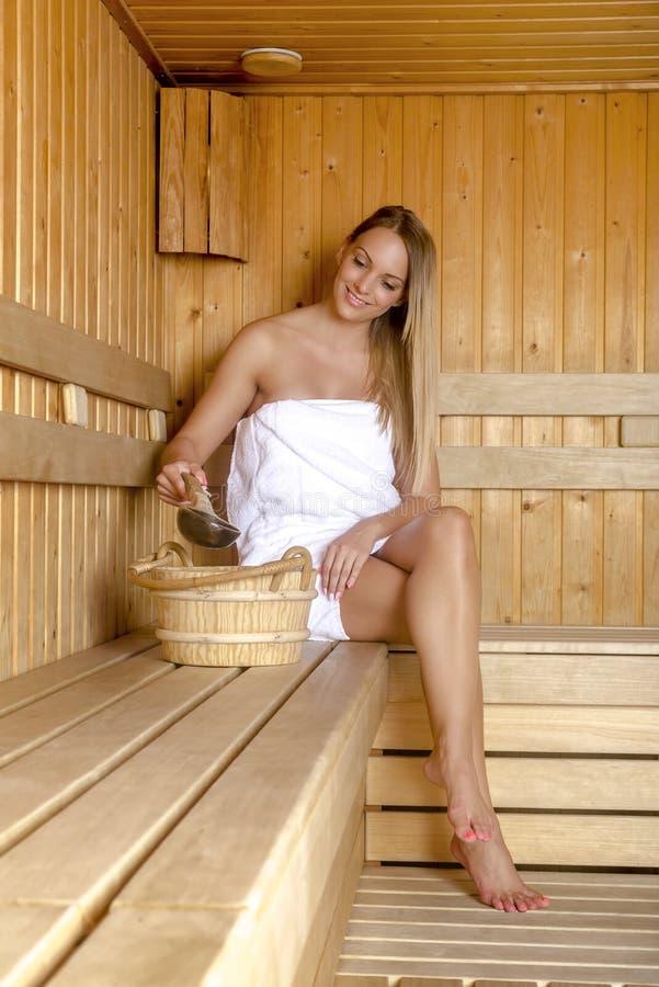 Den unga kvinnan som kopplar av i bastu och, tycker om den varma luften royaltyfria foton