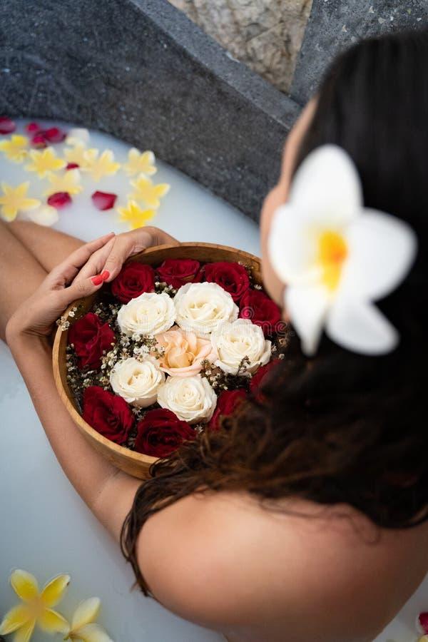 Den unga kvinnan som kopplar av i svart stenbad med tropiska blommor och, steg kronblad Hudbehandling, lyxigt brunnsortbegrepp royaltyfria foton