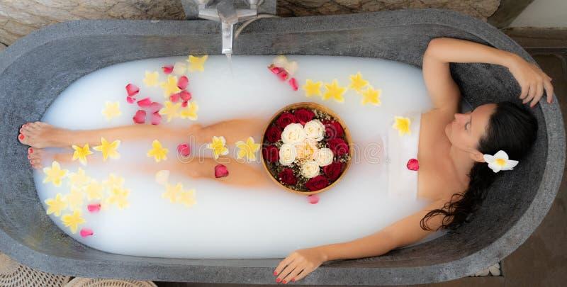 Den unga kvinnan som kopplar av i svart stenbad med tropiska blommor och, steg kronblad Hudbehandling, lyxigt brunnsortbegrepp arkivbild