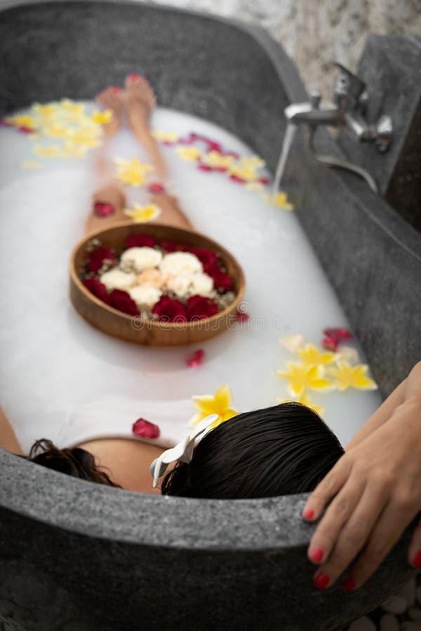 Den unga kvinnan som kopplar av i svart stenbad med tropiska blommor och, steg kronblad Hudbehandling, lyxigt brunnsortbegrepp fotografering för bildbyråer