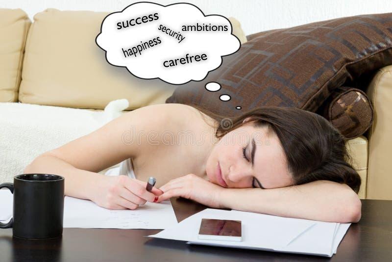 Den unga kvinnan som lär i vardagsrum, är hon trött arkivfoton