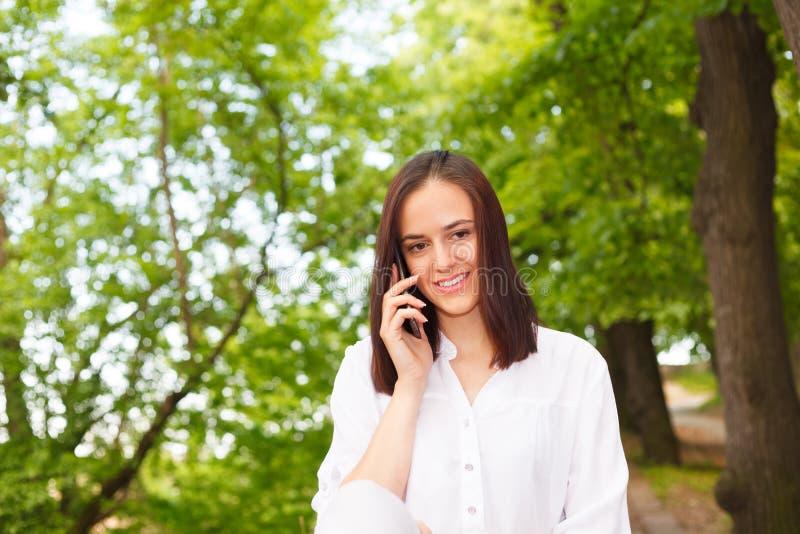 Den unga kvinnan som ler och talar på telefonen i, parkerar royaltyfri bild