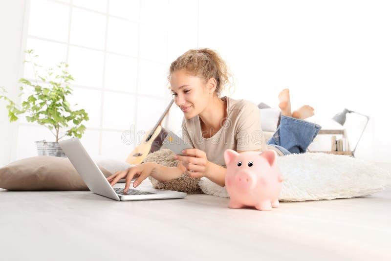 Den unga kvinnan som ler rymma kreditkorten och genom att använda bärbara datorn, beräknar royaltyfri foto