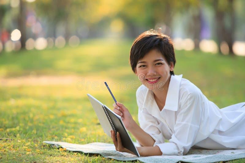 Den unga kvinnan som ligger på grönt gräs, parkerar med blyertspennan och anmärkningsboken royaltyfria bilder
