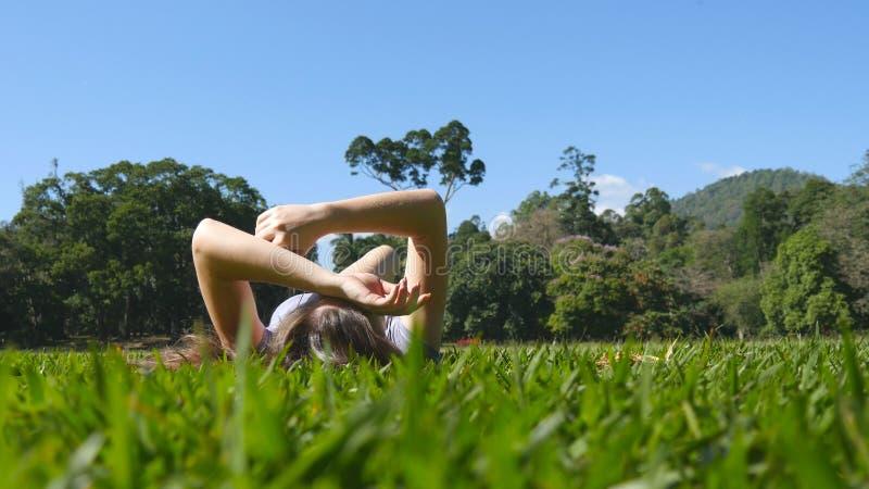 Den unga kvinnan som ligger på grönt gräs parkerar in, och att koppla av Flickasammanträde på äng på naturen och att hålla ögonen arkivbilder