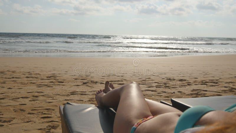 Den unga kvinnan som ligger på, sunbed vid havet och garva Kvinnlig kropp på schäslong som kopplar av och tycker om under sommar royaltyfri fotografi
