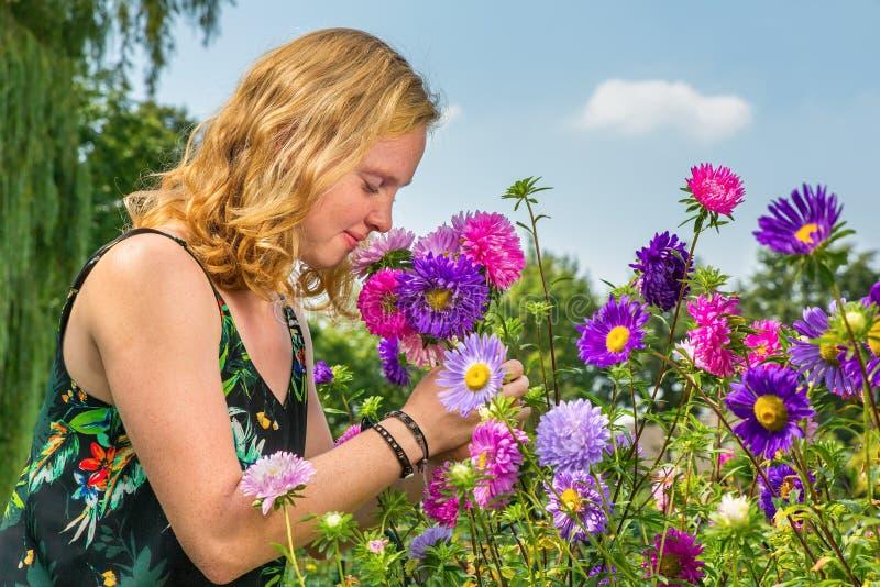 Den unga kvinnan som luktar sommar, blommar i trädgård arkivbilder