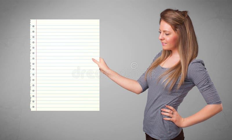 Den unga kvinnan som pappers- hållande vit kopierar utrymme med diagonalen, fodrar royaltyfria foton