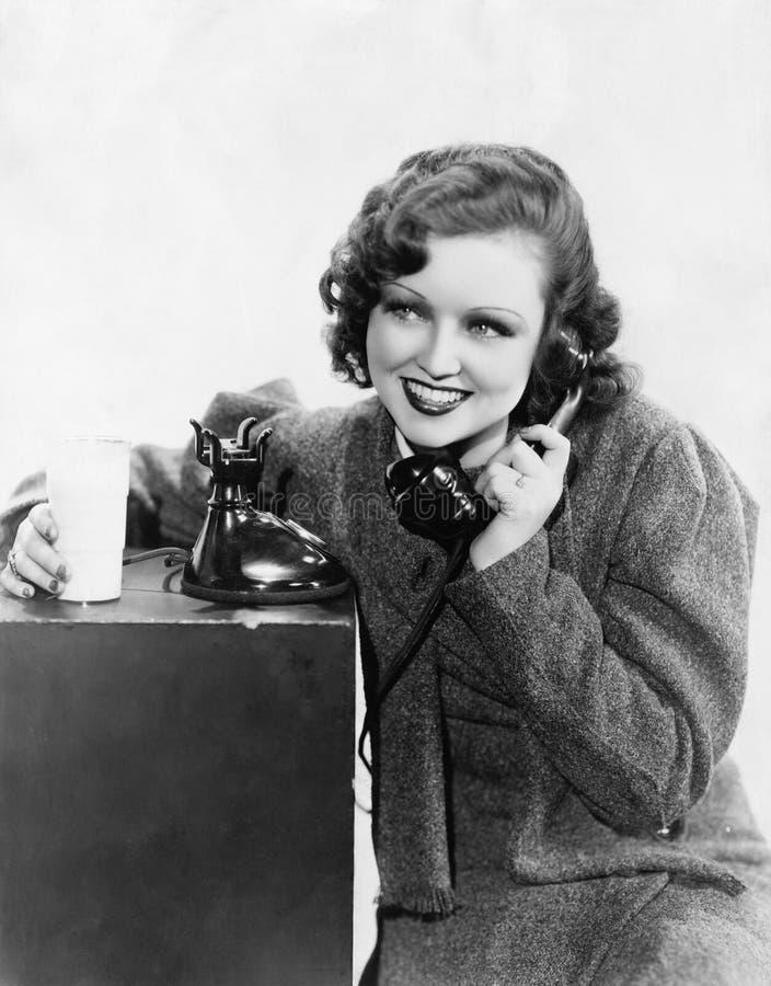 Den unga kvinnan som rymmer ett exponeringsglas av, mjölkar och talar på en roterande telefon (alla visade personer inte är längr fotografering för bildbyråer