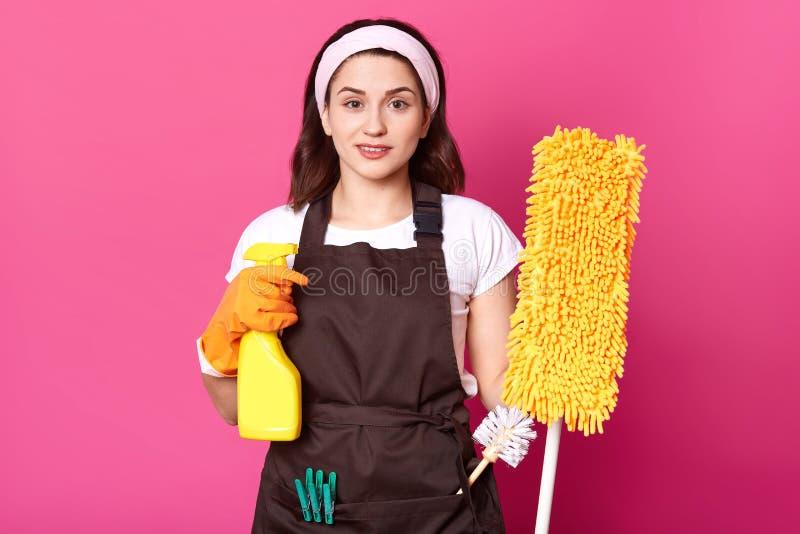 Den unga kvinnan som rymmer gul golvmopp och detegent sprej som förbereder för cleanini hennes hus, har angenämt ansikts- e [pres royaltyfri bild