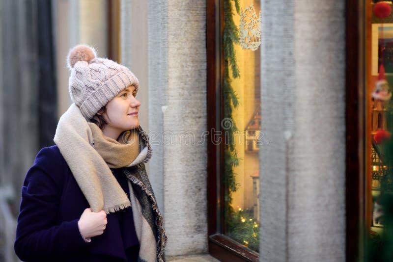 Den unga kvinnan som ser på Xmas-leksaker, och tillbehören på traditionell jul marknadsför i Bayern, Tyskland arkivbild