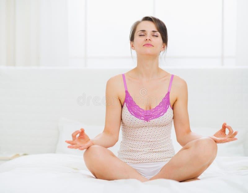 Den unga kvinnan som sitter i yoga, poserar på underlag fotografering för bildbyråer