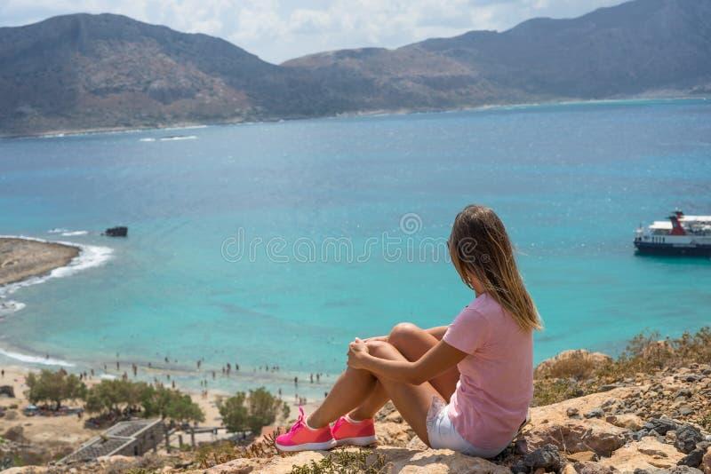 Den unga kvinnan som sitter på ett stort, vaggar och blickar in i avståndet på havet Selektiv mjuk fokus seascape för lagun för b royaltyfria bilder
