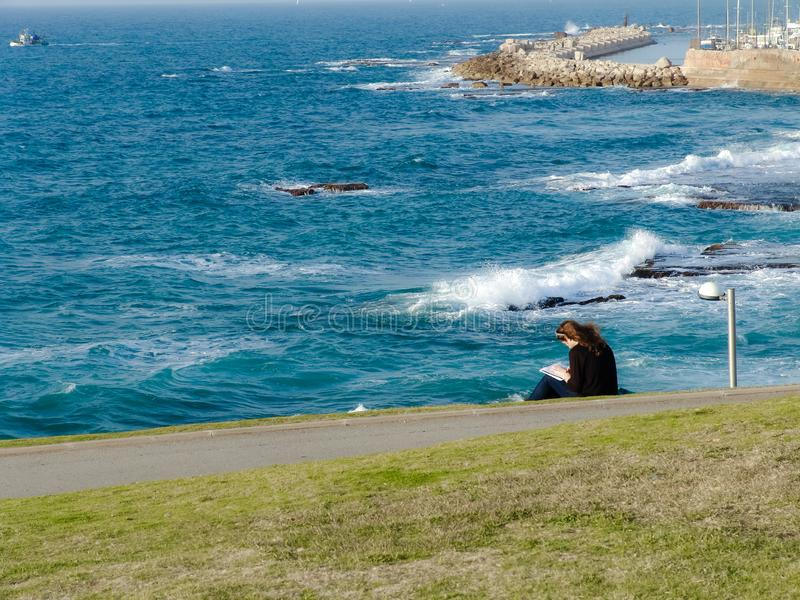 Den unga kvinnan som sitter på grönt gräs på, parkerar, läsning som har uppsikt över en sikt av havet och den Jaffa hamnen royaltyfri fotografi