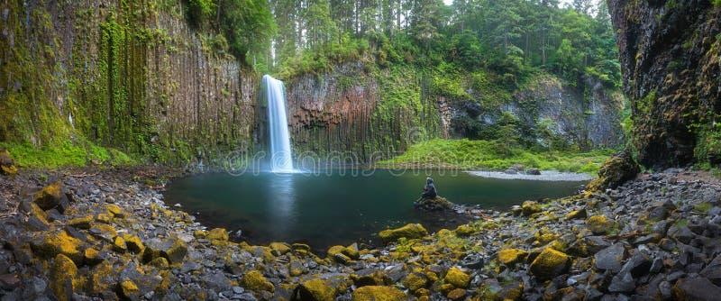 Den unga kvinnan som sitter p?, vaggar p? den h?rliga vattenfallet av Abiqua liten vik, Abiqua nedg?ngar, Oregon, USA royaltyfria foton