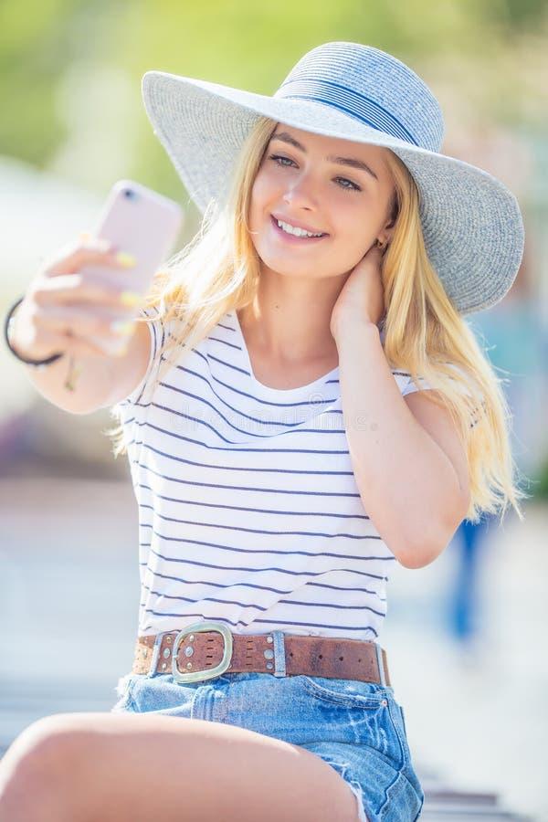 Den unga kvinnan som in sitter, parkerar med smartphonen som gör en selfie Sommarst?ende av den h?rliga ton?riga flickan arkivbild