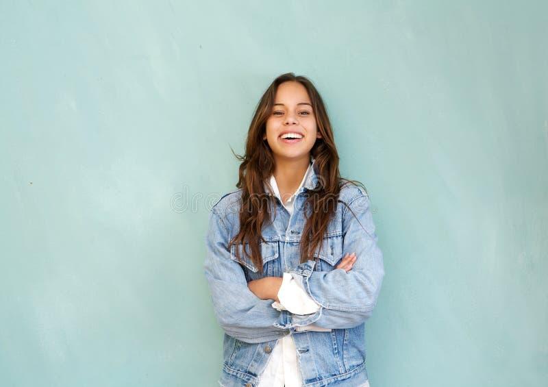 Den unga kvinnan som skrattar med armar, korsade i avkopplat poserar mot blå bakgrund arkivbild
