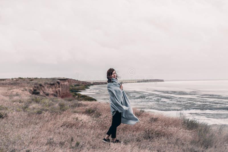 Den unga kvinnan som slås in i varm filt, står på kust av havet i blåsväder royaltyfria bilder