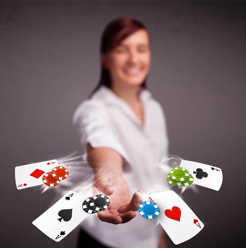 Den unga kvinnan som spelar med poker, cards och gå i flisor royaltyfria bilder