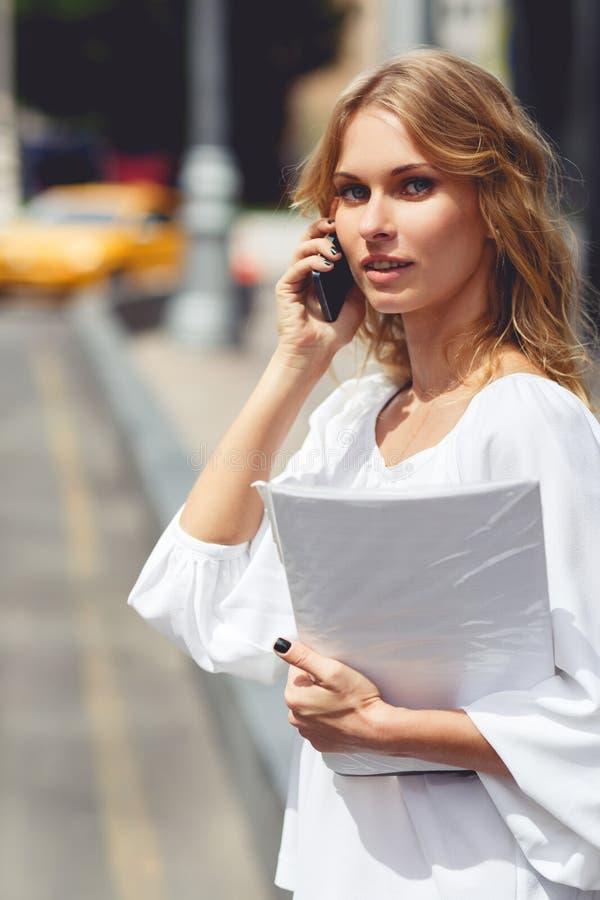 Den unga kvinnan som talar på mobiltelefonen, och innehavet skyler över brister royaltyfri foto