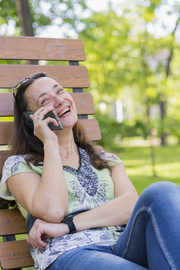 Den unga kvinnan som talar p? smartphonen och skrattar i, parkerar p? b?nken som h?rligt kvinnligt koppla av p? parkerar den b?nk arkivbild