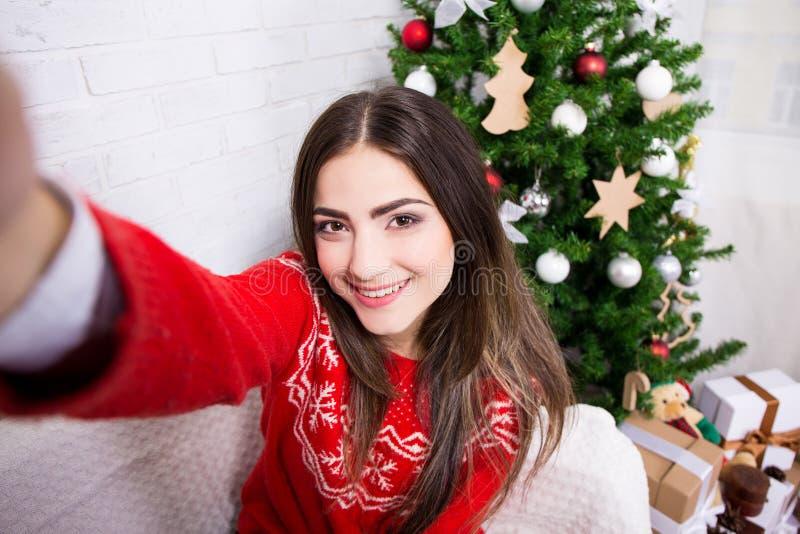 Den unga kvinnan som tar selfiefotoet nära, dekorerade julträdet arkivbilder