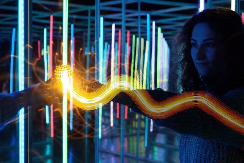 Den unga kvinnan som trycker på hennes reflexion, magiskt guld- ljus, syns arkivbilder
