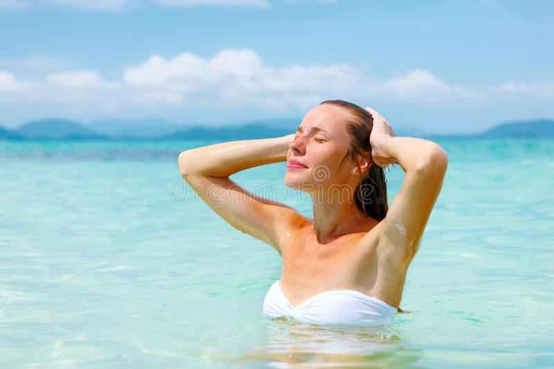 Den unga kvinnan som tycker om att simma i det uppfriskande havet, bevattnar fotografering för bildbyråer