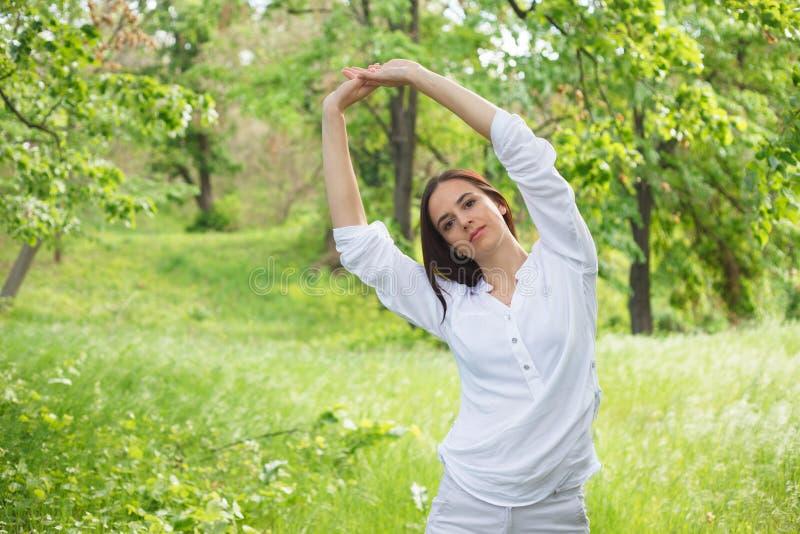 Den unga kvinnan som tycker om naturen i, parkerar royaltyfri bild