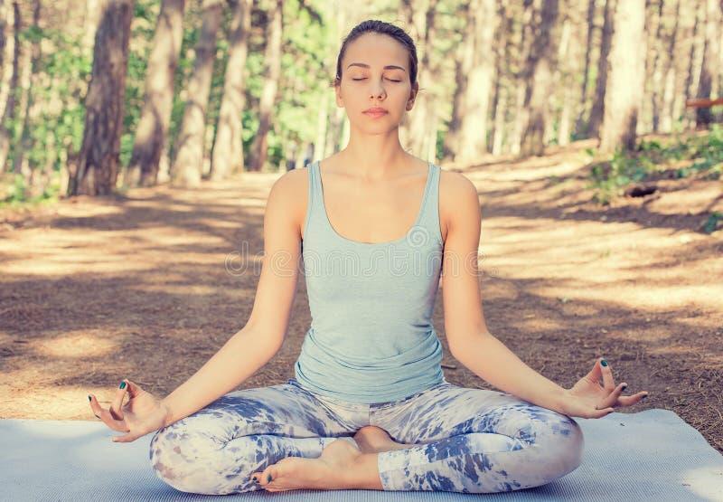Den unga kvinnan som utomhus mediterar i vårsommar, parkerar arkivbild