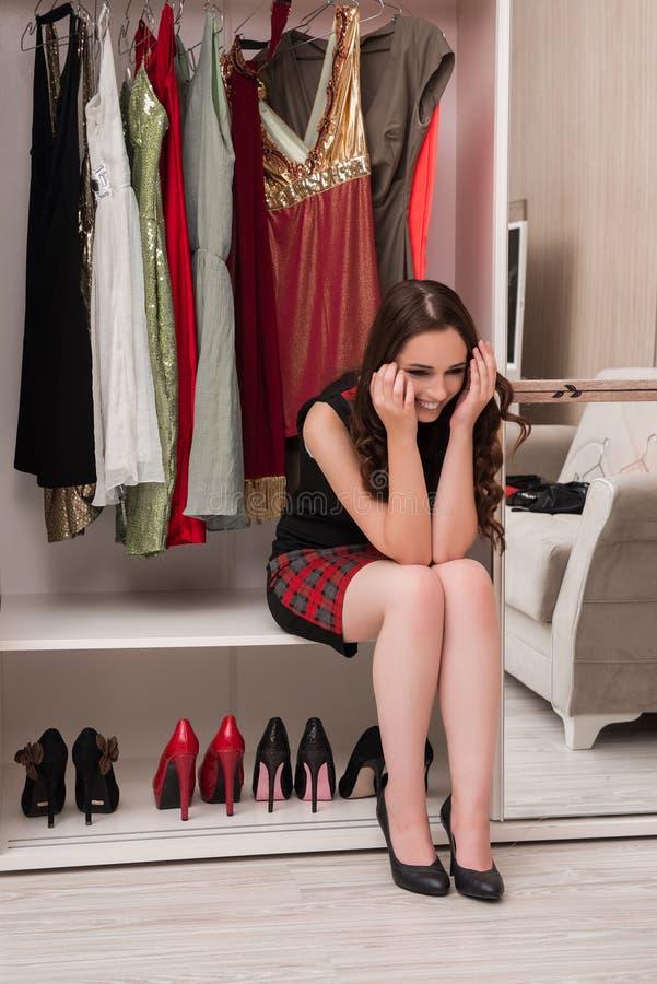 Den unga kvinnan som väljer kläder för aftonparti royaltyfri fotografi