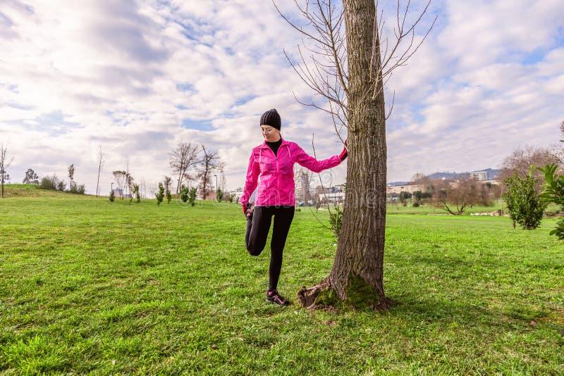 Den unga kvinnan som värmer och sträcker benen upp, för köra på en kall vinter, höst av nedgångdagen i ett stads-, parkerar royaltyfria foton