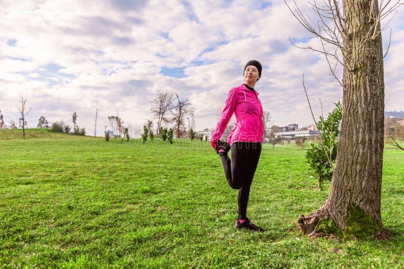 Den unga kvinnan som värmer och sträcker benen upp, för köra på en kall vinter, höst av nedgångdagen i ett stads-, parkerar royaltyfri fotografi