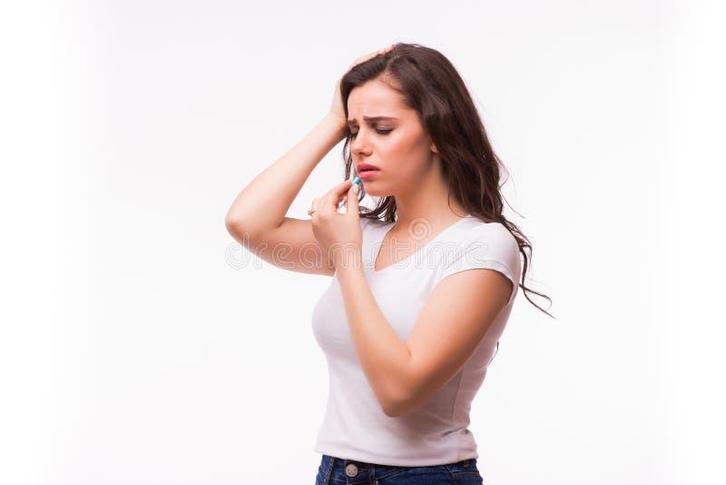 Den unga kvinnan som visar en preventivpiller med det stränga huvudet, smärtar och äter minnestavlan royaltyfria foton