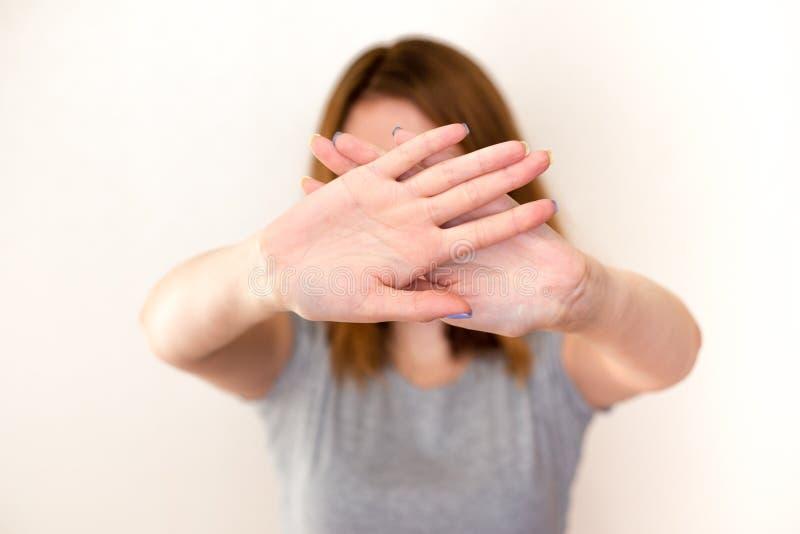 Den unga kvinnan som visar en stoppgest med hennes, gömma i handflatan arkivbilder