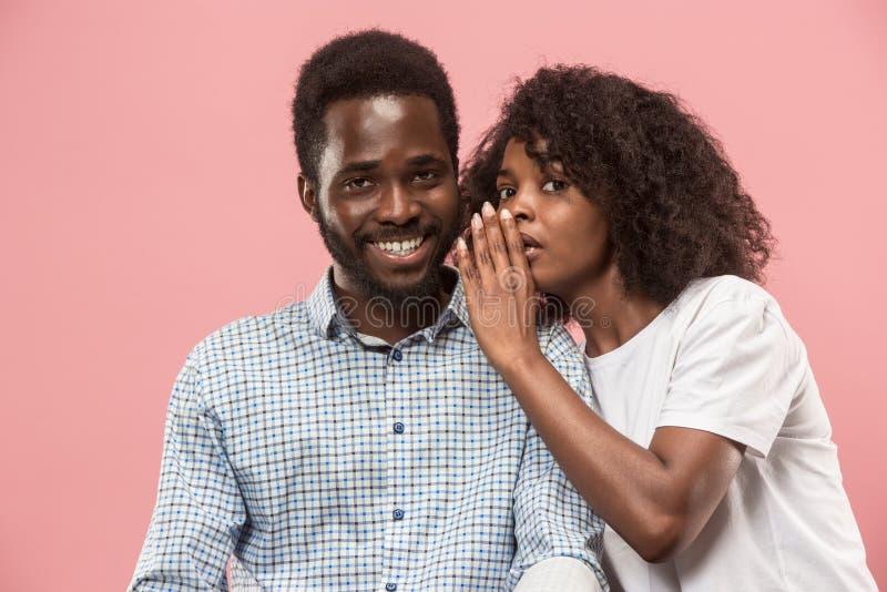 Den unga kvinnan som viskar en hemlighet bak hennes hand till den afro mannen fotografering för bildbyråer