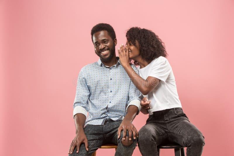 Den unga kvinnan som viskar en hemlighet bak hennes hand till den afro mannen royaltyfri fotografi