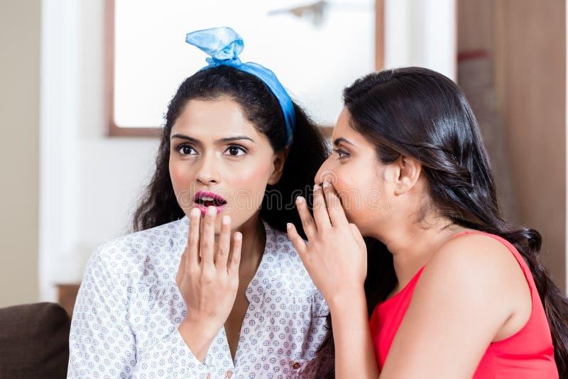 Den unga kvinnan som viskar till hennes bästa vän, skvallrar arkivbild