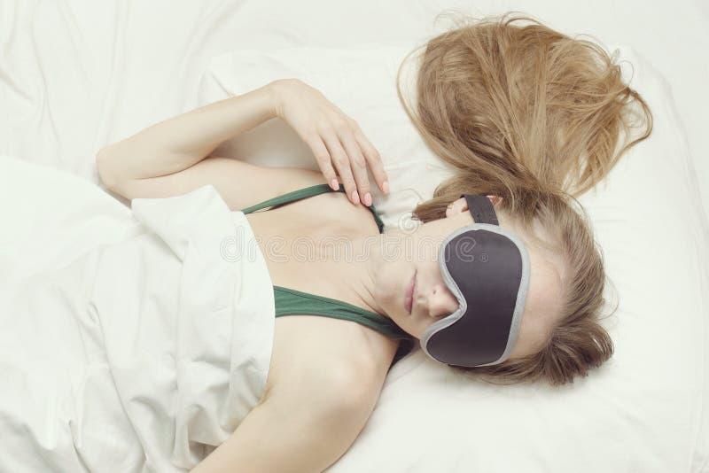 Den unga kvinnan sover i en maskering för sömn avkoppling royaltyfri foto