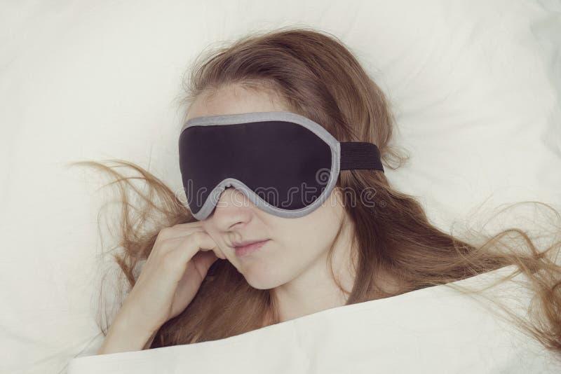 Den unga kvinnan sover i en maskering för sömn avkoppling arkivfoto